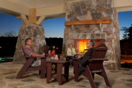 Outdoor fireplace with people gathered around it at Sterling on the Lake